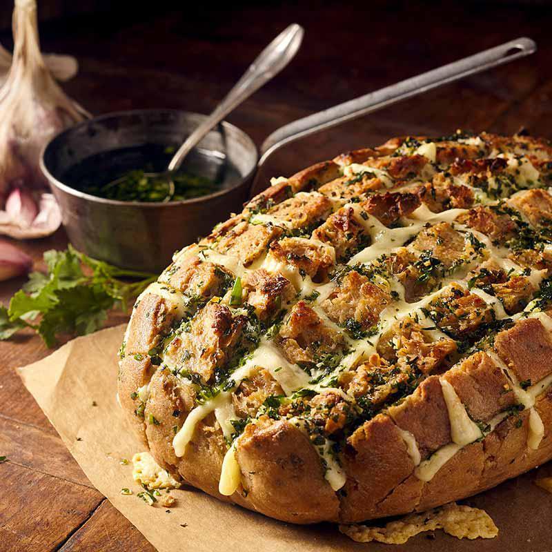 Foto van ingesneden brood gevuld met tuinkruiden en besprenkeld met olijfolie